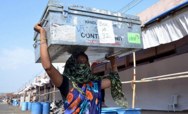 A labourer carries a box contaning election counting material at a counting center in Nagpur...