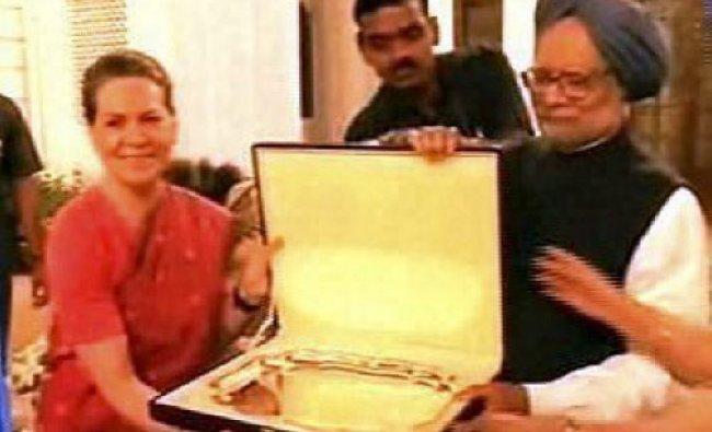 Congress President Sonia Gandhi presents a memento to Prime Minister Manmohan Singh...