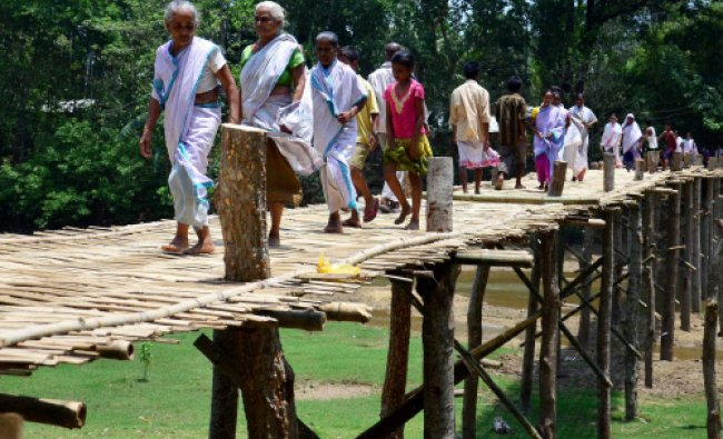 Villagers walk over a newly constructed bamboo bridge at Chaygaon in Kamrup district...