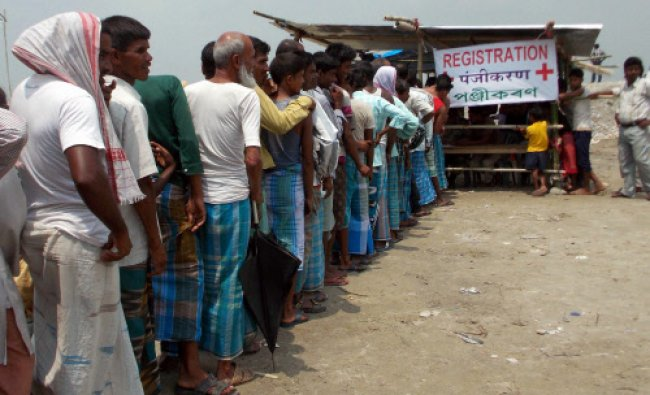 People stand in a queue to get medical help at a relief camp of Narayanguri in violence-hit...