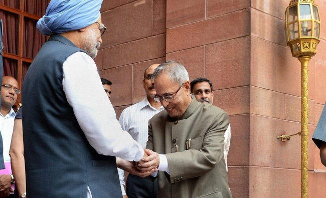 Pranab Mukherjee shakes hands with Prime Minister Manmohan Singh who submitted his resignation ...