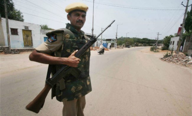 A security person guards in a street at curfew-bound Kisan Bagh in Hyderabad...