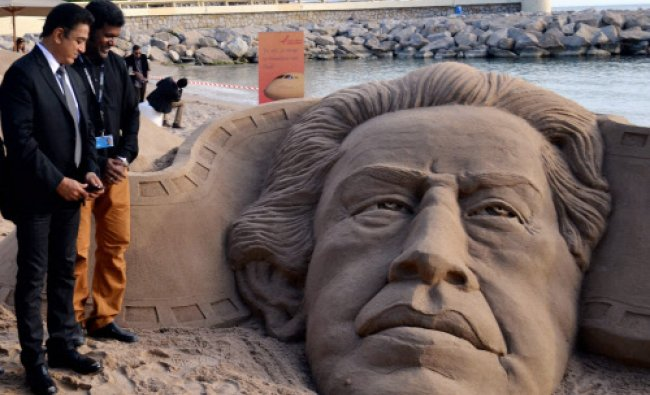 Noted sand artist Sudarsan Pattnaik looks at a sand sculpture of Satyajeet Ray created...