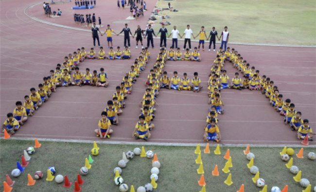 Young football players make a chain that reads \'FIFA\' at Tatya Tope Stadium in Bhopal...