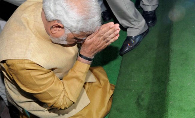 Prime Minister-elect Narendra Modi bends down on the steps of the main entrance of...