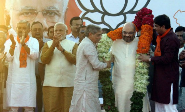 Prime Minister-designate Narendra Modi claps as his close aide Amit Shah is garlanded by...