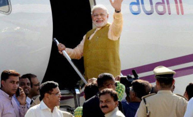 Prime Minister-designate Narendra Modi waves while boarding a flight for Delhi at the ...