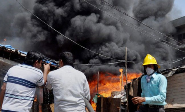Fire tenders dousing a fire that broke out at a godown and jhuggies in Gurgaon on Thursday...