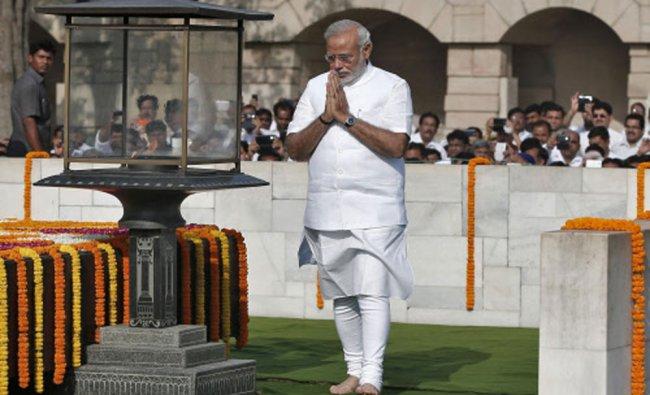 Narendra Modi walks at the Mahatma Gandhi memorial after paying the flower tribute at Rajghat...