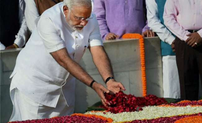 Prime Minister-designate Narendra Modi pays his respects at Rajghat, the memorial of Mahatma...
