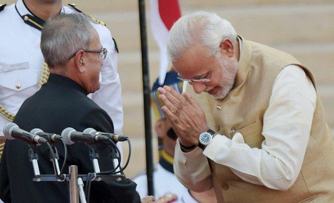 Pranab Mukherjee greets Prime Minister Narendra Modi after administering him the oath ...