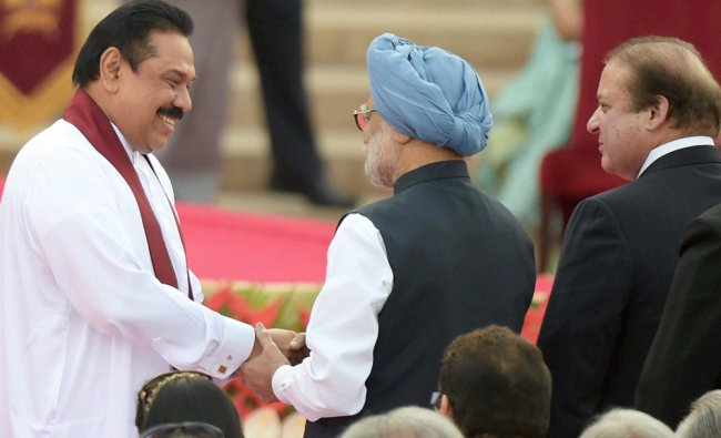 Manmohan Singh shakes hands with Sri Lankan President Mahinda Rajapaksa at the swearing ...