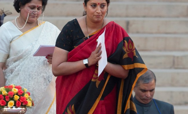 Smriti Irani greets the audience after she takes the oath of office at the presidential palace ...