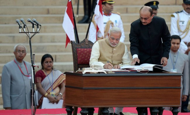Narendra Modi signs the register after taking oath as the 15th Prime Minister of India ...