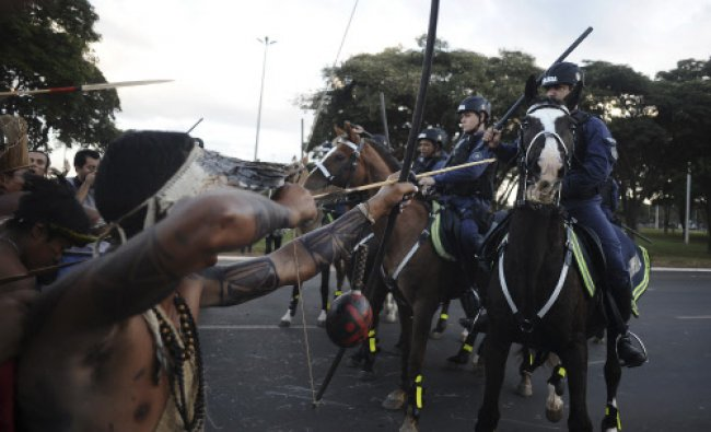 Police confront native Brazilians to impede them from marching towards the Mane Garrincha soccer...