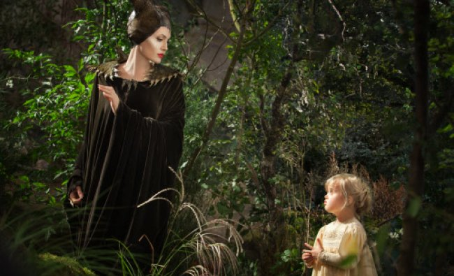This image released by Disney shows Angelina Jolie as Maleficent, left, in a scene with her...