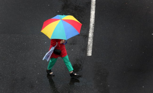 A woman under a colorful umbrella crosses a street in Duesseldorf, Germany, on a rainy Tuesday...