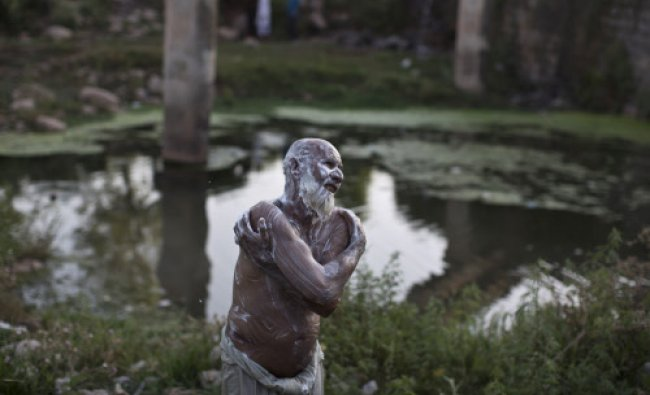 Pakistani vegetables vendor Sher Khan, 55, applies soap on his body while showering near leaking...