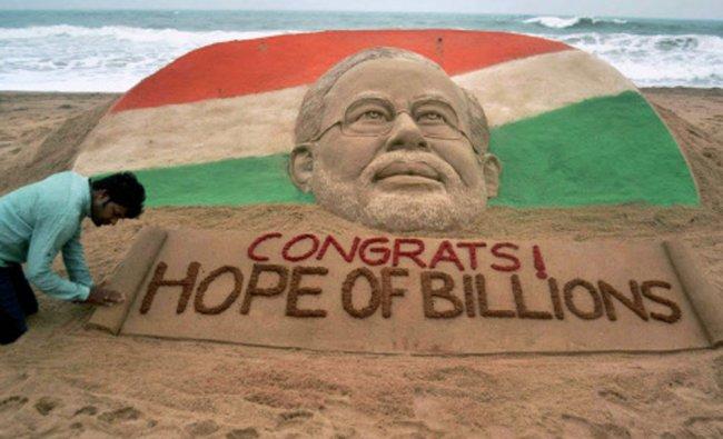 Sand artist Sudarsan pattnaik creates a sand sculpture of Prime Minister Narendra Modi with a...