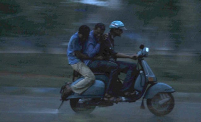 Youngsters triple riding on a scooter in rain near Kukkarahalli Lake in Mysore...