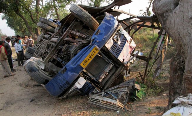 The overturned bus that rammed into a tree at Fatehganj in Bareilly district ...