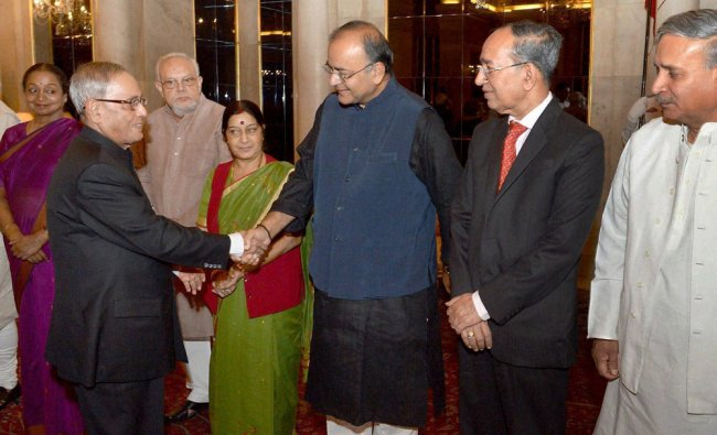 Pranab Mukherjee shakes hand with Finance Minister Arun Jaitley during the dinner hosted ...