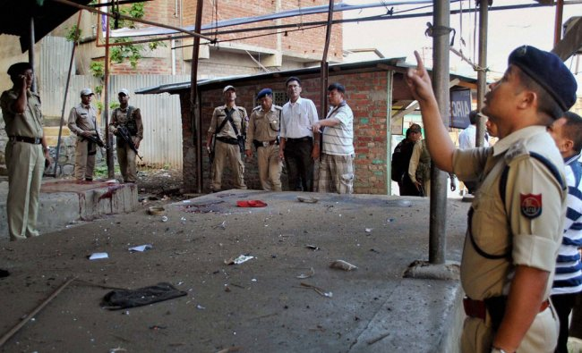 Security men inspect the site of a bomb explosion at Singjamei Chingamakhong in Imphal ...