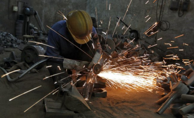 A worker grinds a metal shaft metal used in water pumps at a manufacturing unit on the outskirts...