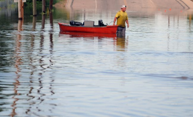 A man uses a boat to remove items from a business in Greeley, Colo., Monday, June 2, 2014. About...