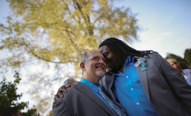 Hank Hamilton hugs his partner Larry Clement (L) after their same-sex marriage ceremony in a mass...