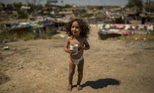 A girl walks barefoot holding a cup reading \'I was in Benicasim\' in her shanty town on the...