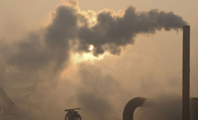 Smoke emitted from chimneys of a cement plant in Binzhou city, in eastern China\'s Shandong...