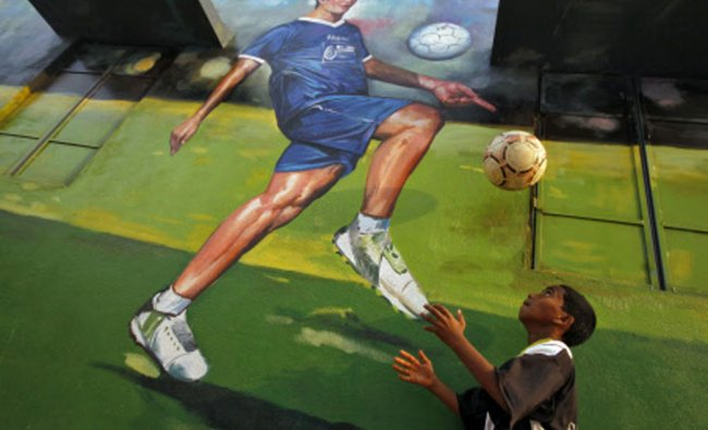 A boy heads a soccer ball in front of a mural of India\'s former captain Baichung Bhutia at a...