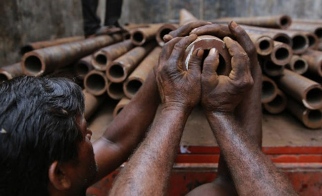 Laborers load iron pipes on to a truck at an iron and steel forging unit in Mumbai...