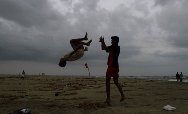 Boys practice somersaulting on a beach against the backdrop of pre-monsoon clouds, Kochi June 3...