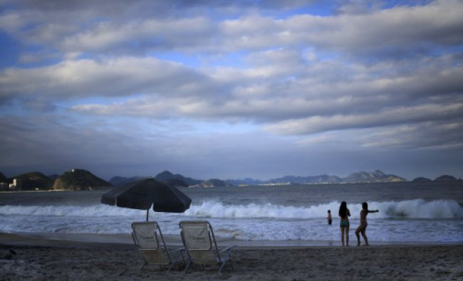Tourists enjoy the sun set on Copacabana beach in Rio de Janeiro, Brazil, Tuesday, June 3, 2014....