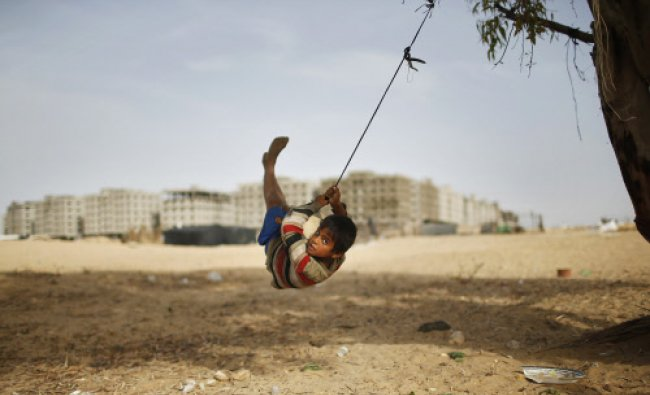 A Palestinian boy swings on a rope tied on a tree at a former Jewish settlement in Khan Younis in...