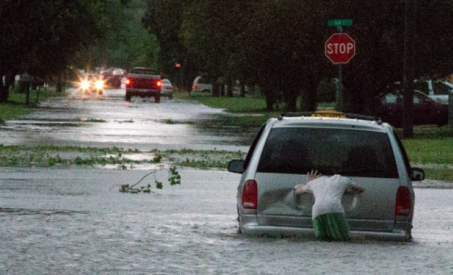 A man tries to push a cab from standing water near North 17th Street and Ave J in Council Bluffs...