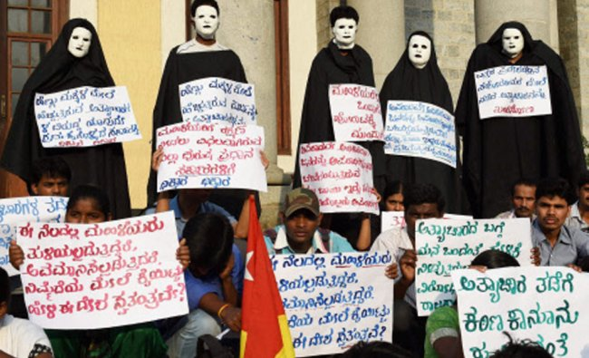 Activists of campaign against sexual assault and rape (CASAR) wear black cloths and masks as they...