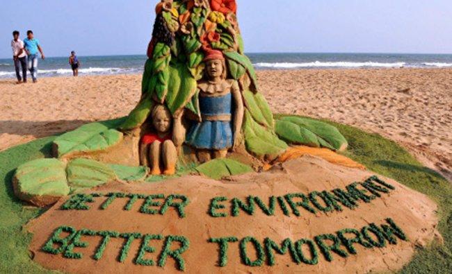 Sand artist Manas Sahoo creates a sand sculpture on World Environment Day at Puri beach on....
