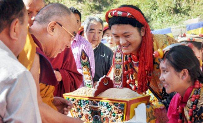Tibetan spiritual leader the Dalai Lama is welcomed as he arrives at a village school in...