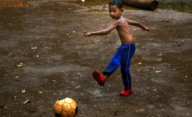 A boy playing soccer during the first pre monsoon showers, in Mumbai,Wednesday...