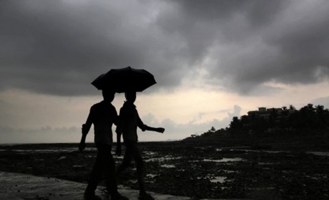 Boys hold an umbrella as they watch the first pre monsoon showers in Mumbai, Wednesday...