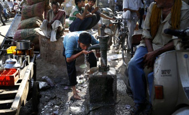 A laborer quenches his thirst from a roadside tube well at a wholesale market on a hot summer...