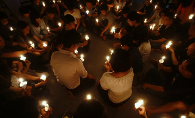 People hold candles during a candlelight vigil to commemorate the 25th anniversary of the June 4...