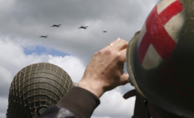 An history enthusiast takes a picture of U.S. Air Force C-47 Skytrain aircraft as they fly over...
