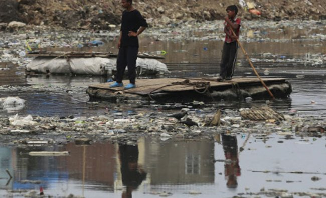 A boy guides a raft through a polluted canal littered with plastic bags and other garbage on...