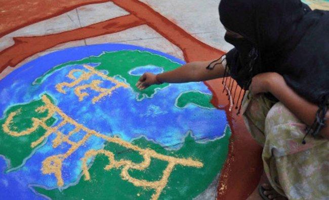 A woman makes a \'rangoli\' on World Environment Day in Moradabad on Thursday...