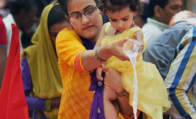 A Kashmiri Pandit woman along with her kid offering prayers at the famous Kheer Bhawani ...