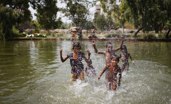 Children play in a pond on a hot summer afternoon in New Delhi, Friday, June 6, 2014...